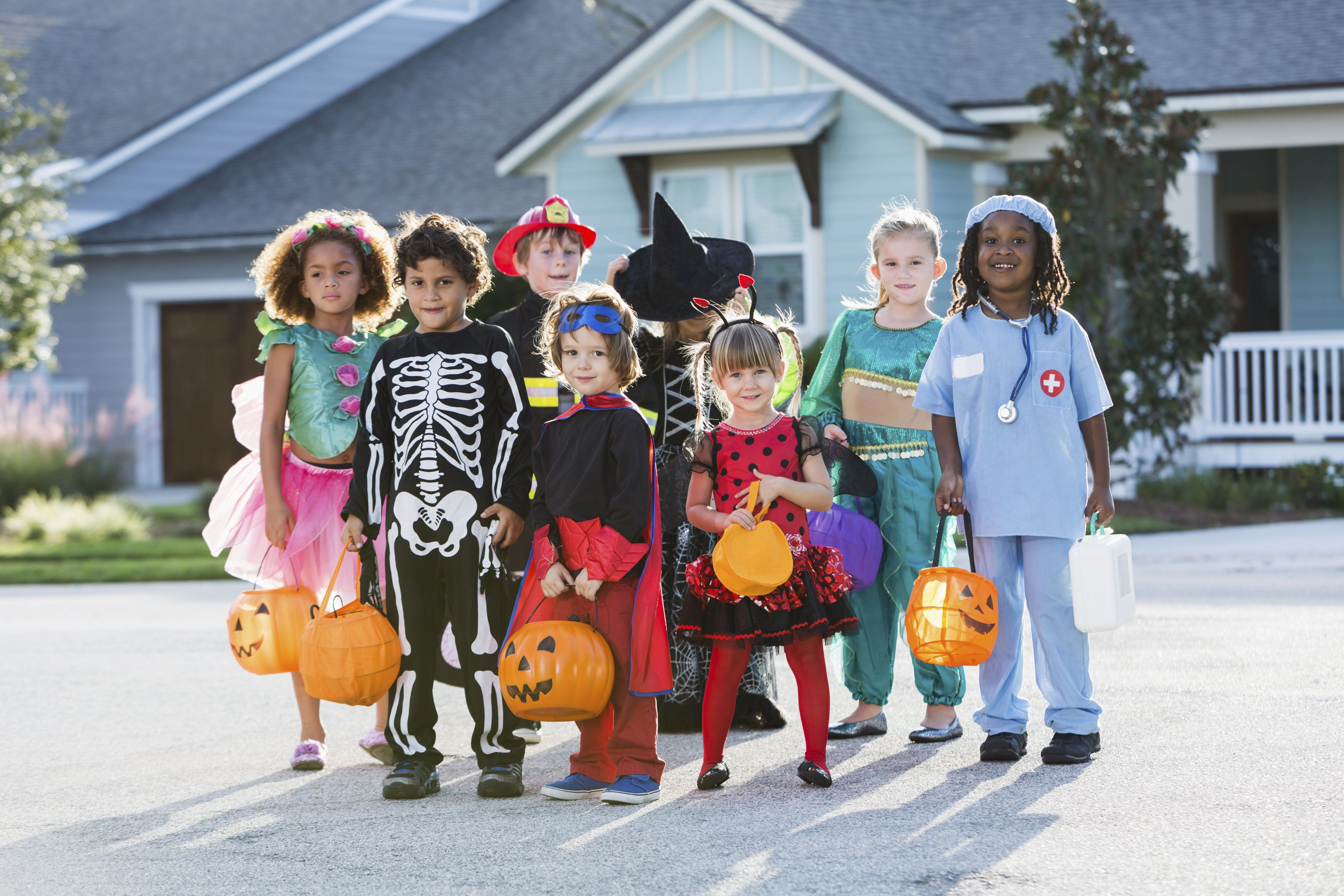 Multi-ethnic group of children 3-6 years old, wearing halloween costumes.