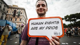 ROME, ITALY - 2015/06/13: A participants holds a banner reading' Human rights are my pride' during the 21st annual Gay Pride Parade in Rome. Tens of thousands of members of Italian LGBTQI communities and supporters of gay rights take part in the 21st annual Gay Pride Parade in downtown Rome to demand legal rights for same-sex couples and against homophobia. (Photo by Giuseppe Ciccia/Pacific Press/LightRocket via Getty Images)