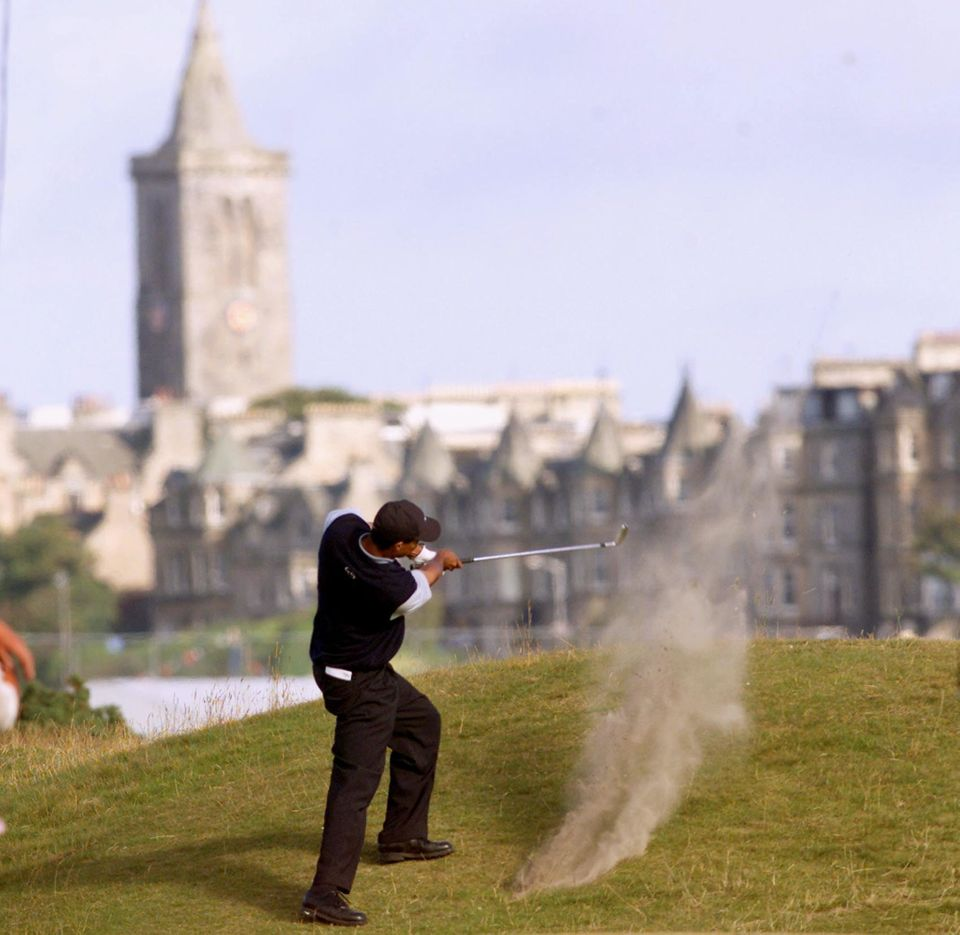 ST. ANDREWS, UNITED KINGDOM:  With the town of St. Andrews in the distance, Tiger Woods of the US hits onto the 16th green fr