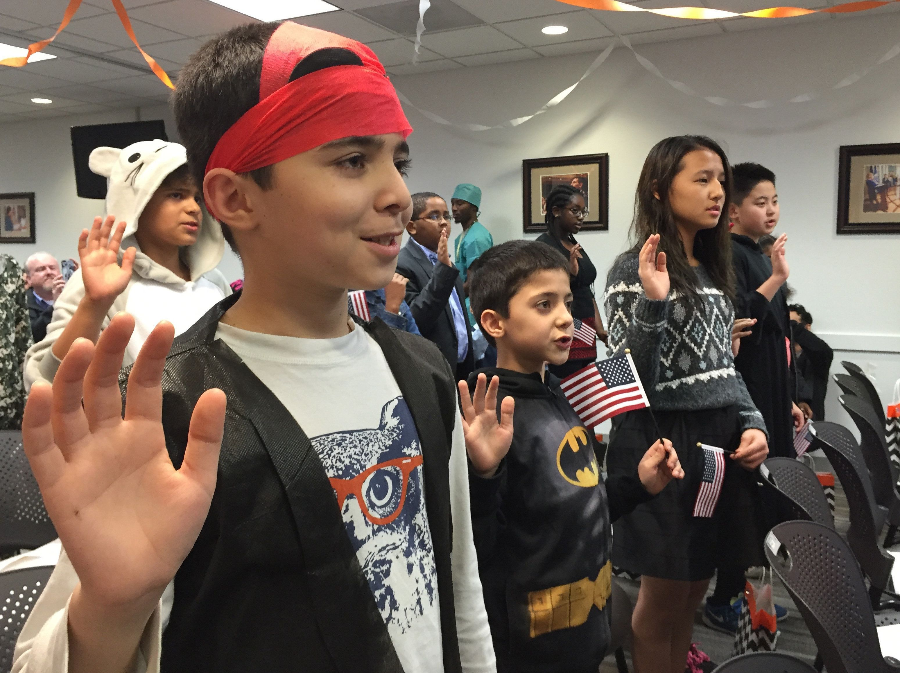Ahad Kahattak, 11, and Ahmad Kahattak, 8, of Pakistan take the oath of allegiance during a U.S. naturalization ceremony.