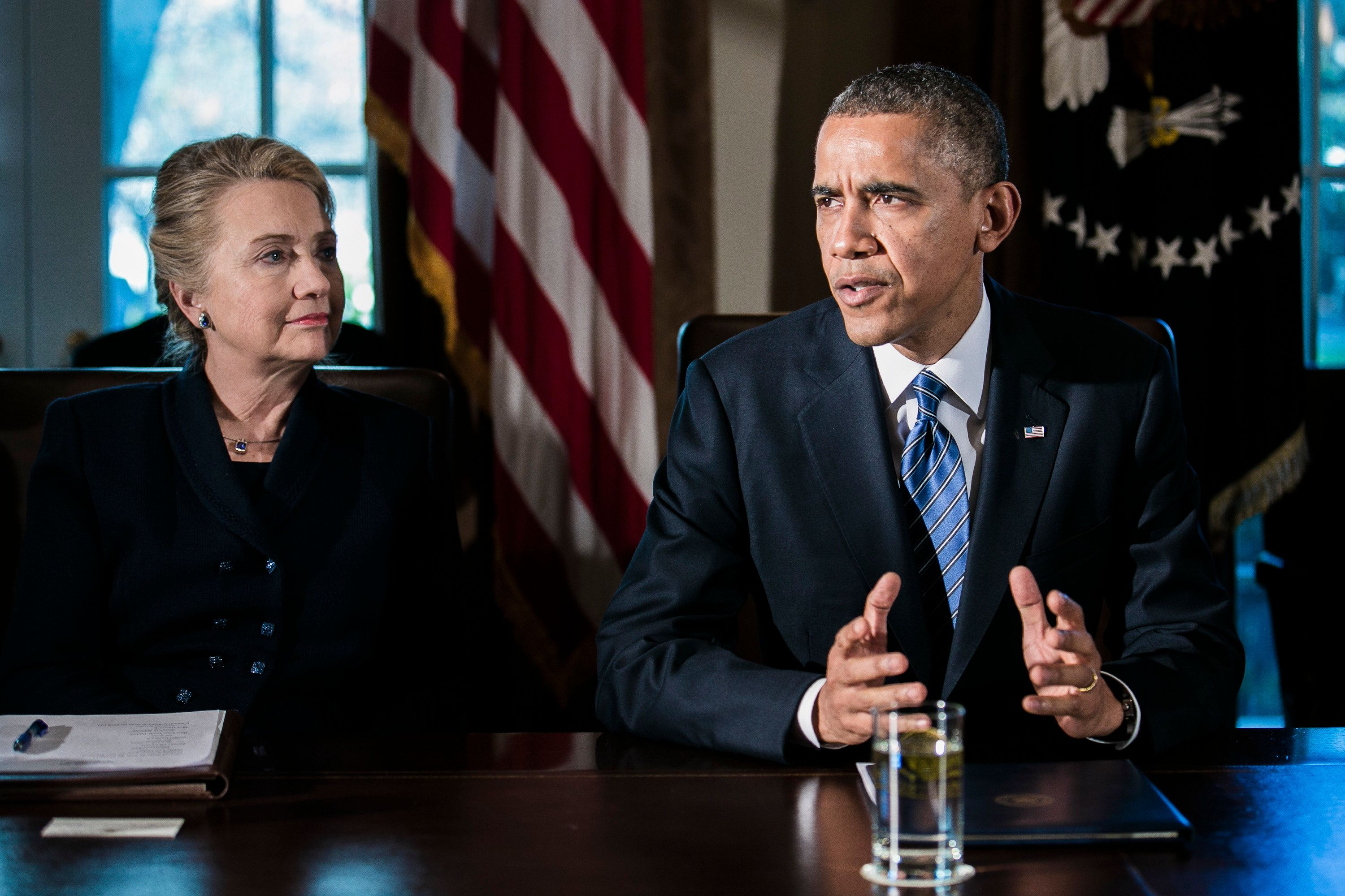 Hillary Clinton, U.S. secretary of state, left, listens while President Barack Obama speaks during a cabinet meeting at the White House in Washington, D.C., U.S., on Wednesday, Nov. 28, 2012. Business executives pressing for a solution to the so-called fiscal cliff made  their case at the White House and the Capitol a day after Senate Majority Leader Harry Reid lamented the lack of progress toward a deal. Photographer: T.J. Kirkpatrick/Bloomberg via Getty Images