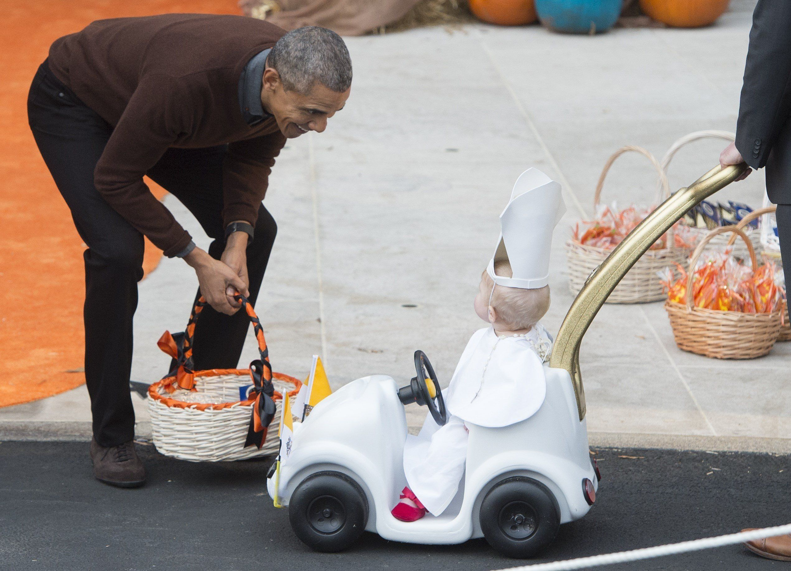 US President Barack Obama greets a young child dressed as the Pope and riding in a 'Popemobile' as he hands out treats to children trick-or-treating for Halloween on the South Lawn of the White House in Washington, DC, October 30, 2015. AFP PHOTO / SAUL LOEB        (Photo credit should read SAUL LOEB/AFP/Getty Images)