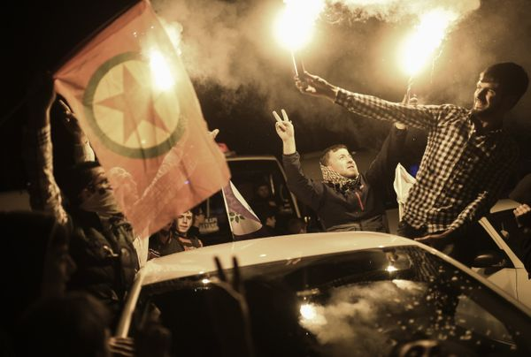 Pro-Kurdish party supporters celebrate with fireworks and flares.