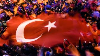 Supporters of Turkey's Justice and Development Party (AKP) wave a giant Turkish flag as they celebrate in Istanbul after the first results in the country's general election on November 1, 2015. Turkey's long-dominant Justice and Development Party (AKP) scored a stunning electoral comeback, regaining its parliamentary majority in a poll seen as crucial for the future of the troubled country. AFP PHOTO / OZAN KOSE        (Photo credit should read OZAN KOSE/AFP/Getty Images)