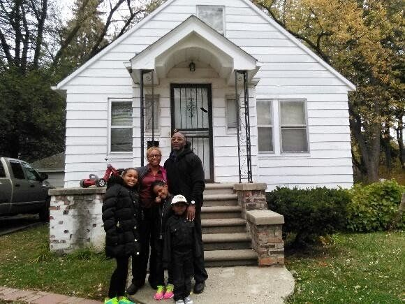 Tynetta Sneed, her three children and herfiancé stand in front of their home in northwest Detroit.