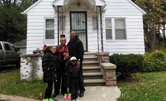 Tynetta Sneed, her three children and her fiancé stand in front of their home in northwest Detroit.