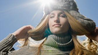 Portrait of young stylish woman in fur hat looking at camera