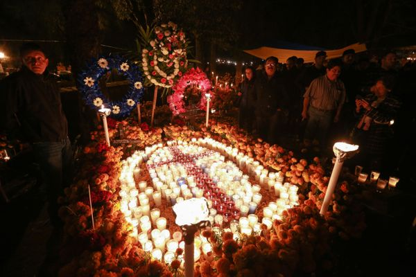Families decorate a relative's grave with flowers at a cemetery in Tzintzuntzan, Michoacan State, Mexico.