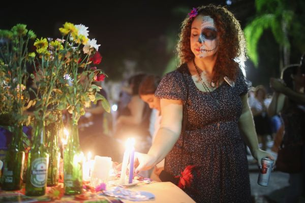 A reveler places a candle during a Day of the Dead party on November 1, 2015 in Rio de Janeiro, Brazil. Brazilians often mark