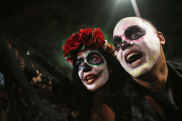 Revelers embrace while posing during a Day of the Dead party on November 1, 2015 in Rio de Janeiro, Brazil.