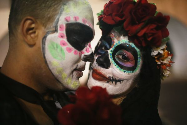 Revelers look on while posing during a Day of the Dead party on November 1, 2015 in Rio de Janeiro, Brazil.