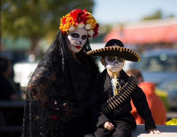 Stacy Waters and Rhoman wait to join the processional parade during the Dia de los Muertos (Day of the Dead) celebration, Nov