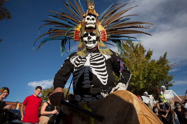 Martin Vera, dressed in a traditional Aztec head dress, joins in the processional parade during the Dia de los Muertos (Day o