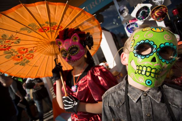 Ben and Kayle Kissler wait for the processional parade during the Dia de los Muertos (Day of the Dead) celebration, November