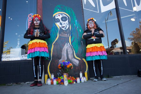 Adrina Trejo and Moses Duran pose for photos at an ofrenda during the Dia de los Muertos (Day of the Dead) celebration, Novem