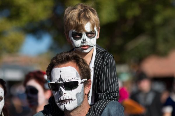A young boy rides on his father's shoulders during the Dia de los Muertos (Day of the Dead) celebration, November 1, 2015 in