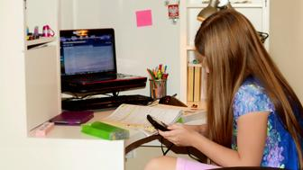 Young girl doing her homework. She is solving math problems using calculator.