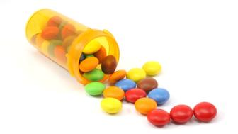 Candy spilling out of pill bottle