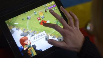 A woman plays the Clash of Clans game of Finnish computer game maker Supercell on a tablet computer on December 14, 2012 in Helsinki. Finnish computer game maker Supercell has sold control of the company for 1.1-billion-euro ($1.5 billion) to two Japanese investors, SoftBank and GungHo, the Helsinki-based company announced on its website on October 15, 2013. AFP PHOTO / Lehtikuva/VESA MOILANEN    FINLAND OUT        (Photo credit should read VESA MOILANEN/AFP/Getty Images)