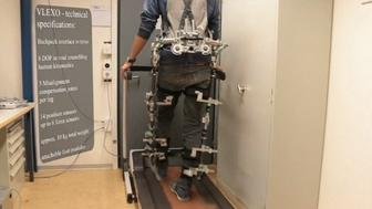 A researcher walks in an exoskeleton prototype.
