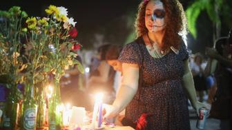 RIO DE JANEIRO, BRAZIL - NOVEMBER 01:  A reveler places a candle during a Day of the Dead party on November 1, 2015 in Rio de Janeiro, Brazil. Brazilians often mark the traditional Mexican holiday by visiting loved ones' graves and sometimes leaving offerings of food or drink. The day officially falls tomorrow in Brazil and is a national holiday.  (Photo by Mario Tama/Getty Images)