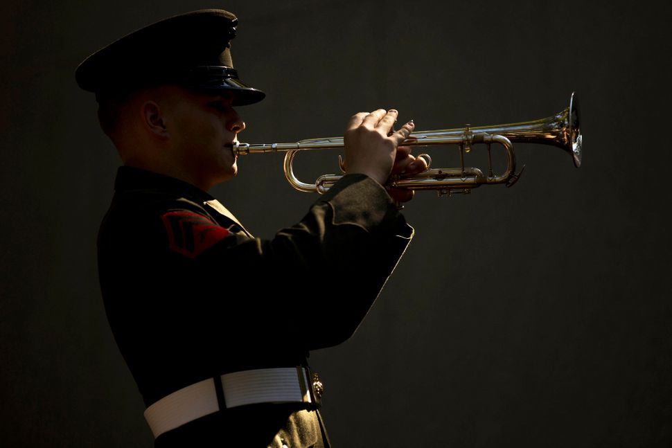 Corporal Derek Detzler, a bugler with the 2nd Marine Division Band, performs Taps during the 32nd Beirut Memorial Observance