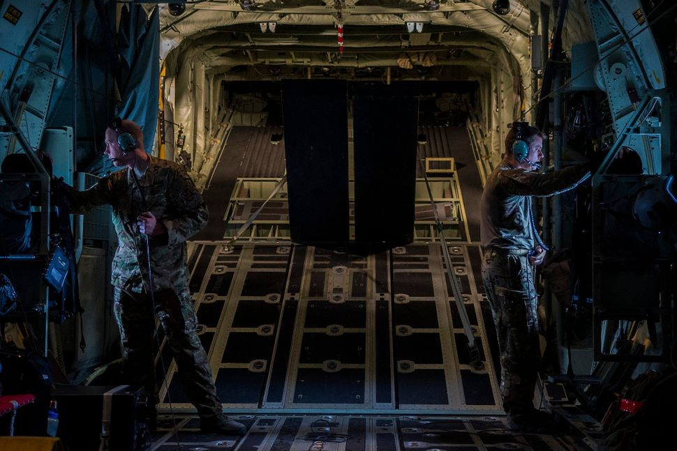 Two Airmen, assigned to the 71st Rescue Squadron at Moody Air Force Base, Ga., look out the windows of a C-130J Super Hercule