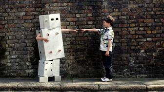 Two children (7-9) pointing towards one another, girl dressed as robot