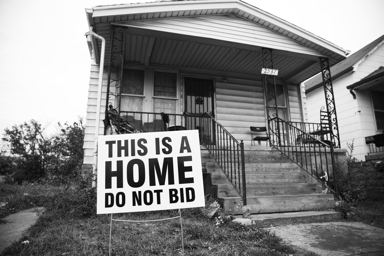 The Tricycle Collective gave families yard signs to dissuade people from bidding on their homes in the auction.