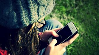 A teenager holding and using a mobile phone.