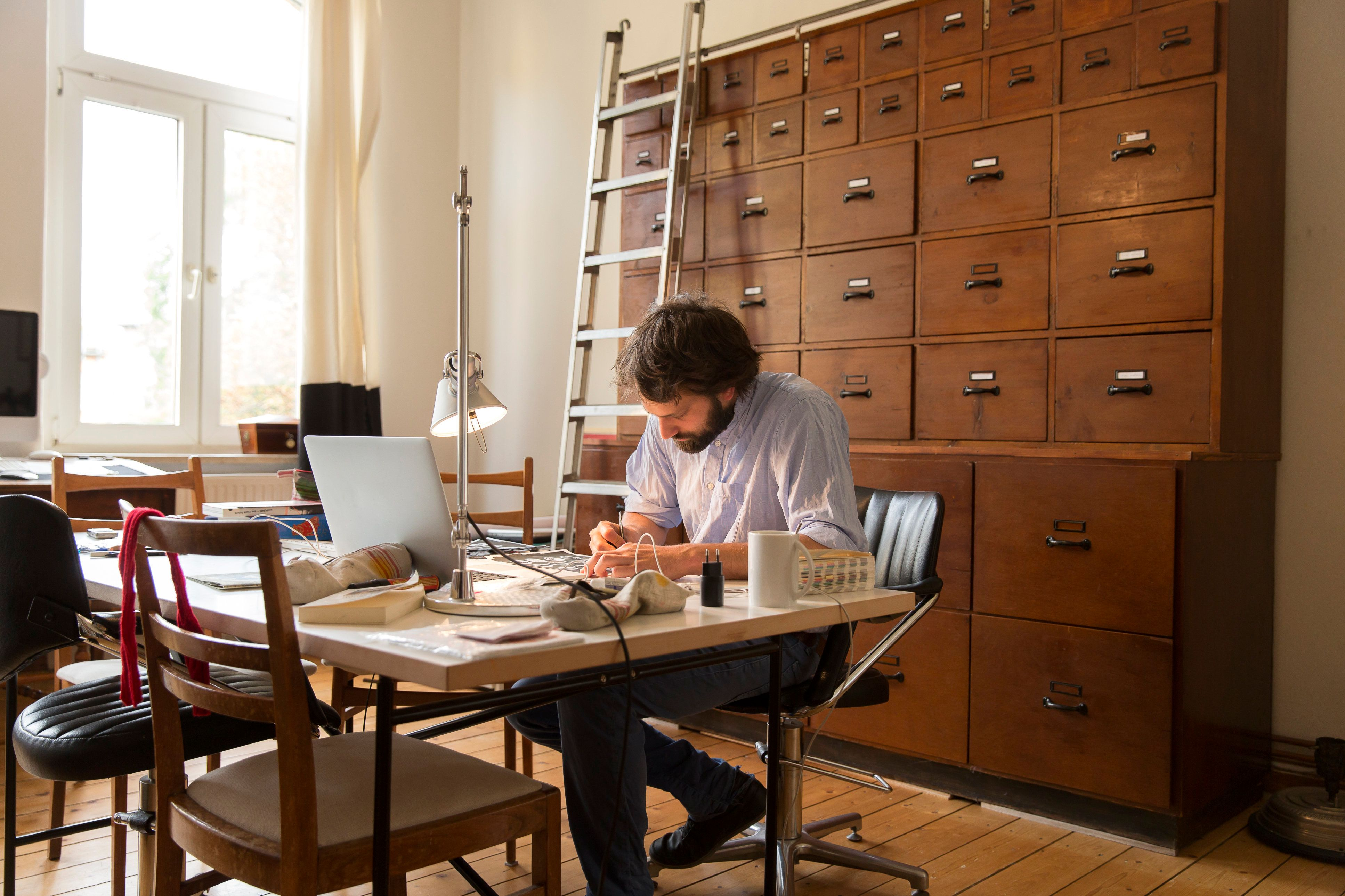 Young designer working in home office.
