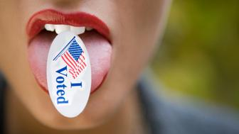 Detail of young woman sticking out tongue with I Voted sticker