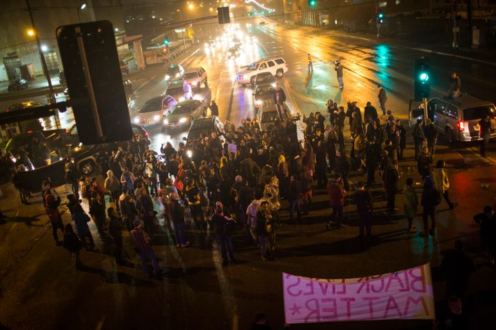 Demonstrators block traffic at an intersection as they march through St. Louis streets protesting the killing of Michael Brow