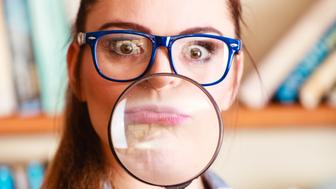 Investigation exploration education concept. Closeup funny student girl in library, woman in eyeglasses holding magnifying glass loupe