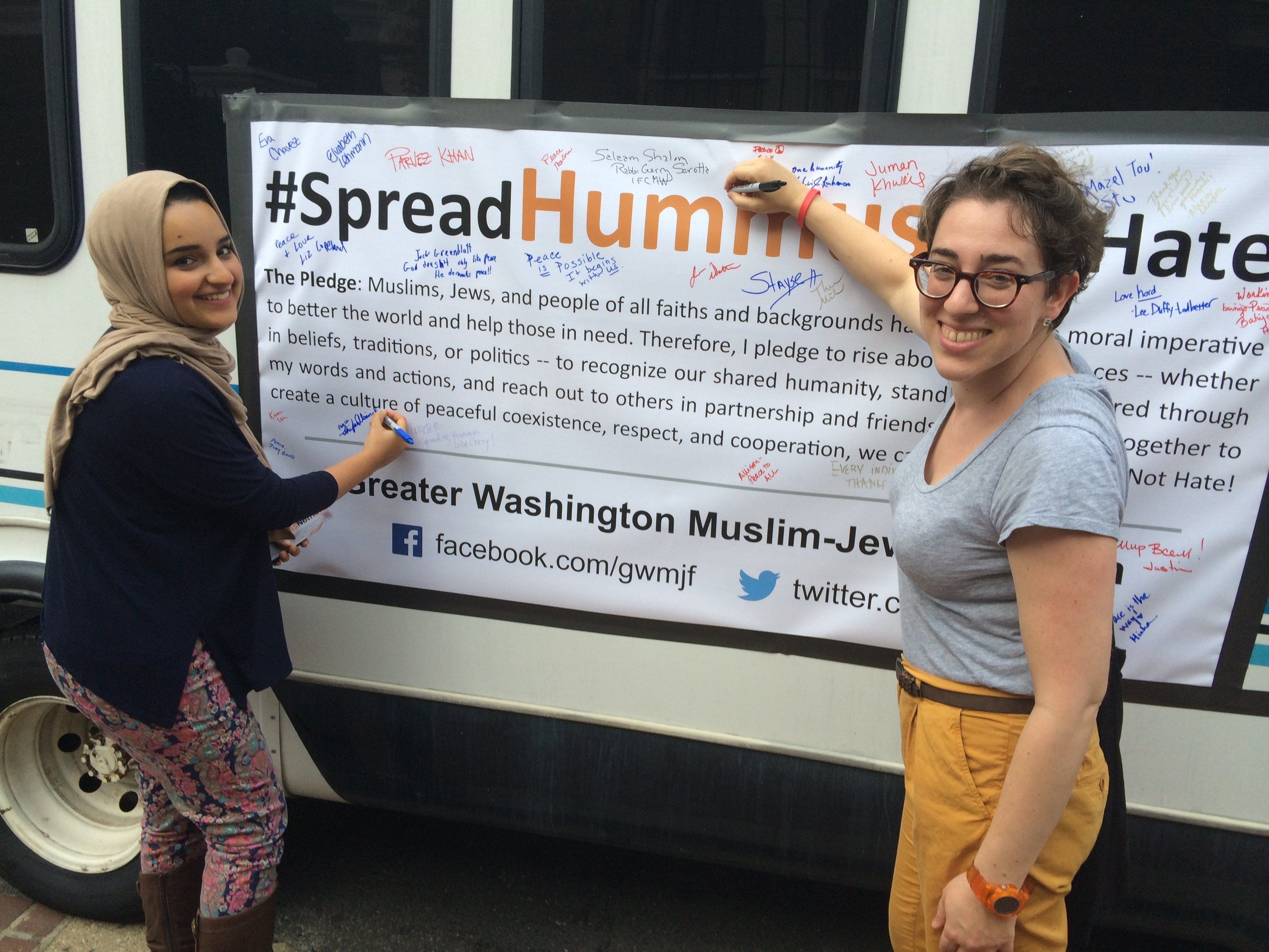 """""""Spread Hummus Not Hate"""" organizer Symi Rom-Rymer signs apledge of peace with a Muslim student from the University of M"""