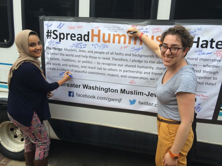 """Spread Hummus Not Hate"" organizer Symi Rom-Rymer signs a pledge of peace with a Muslim student from the University of M"