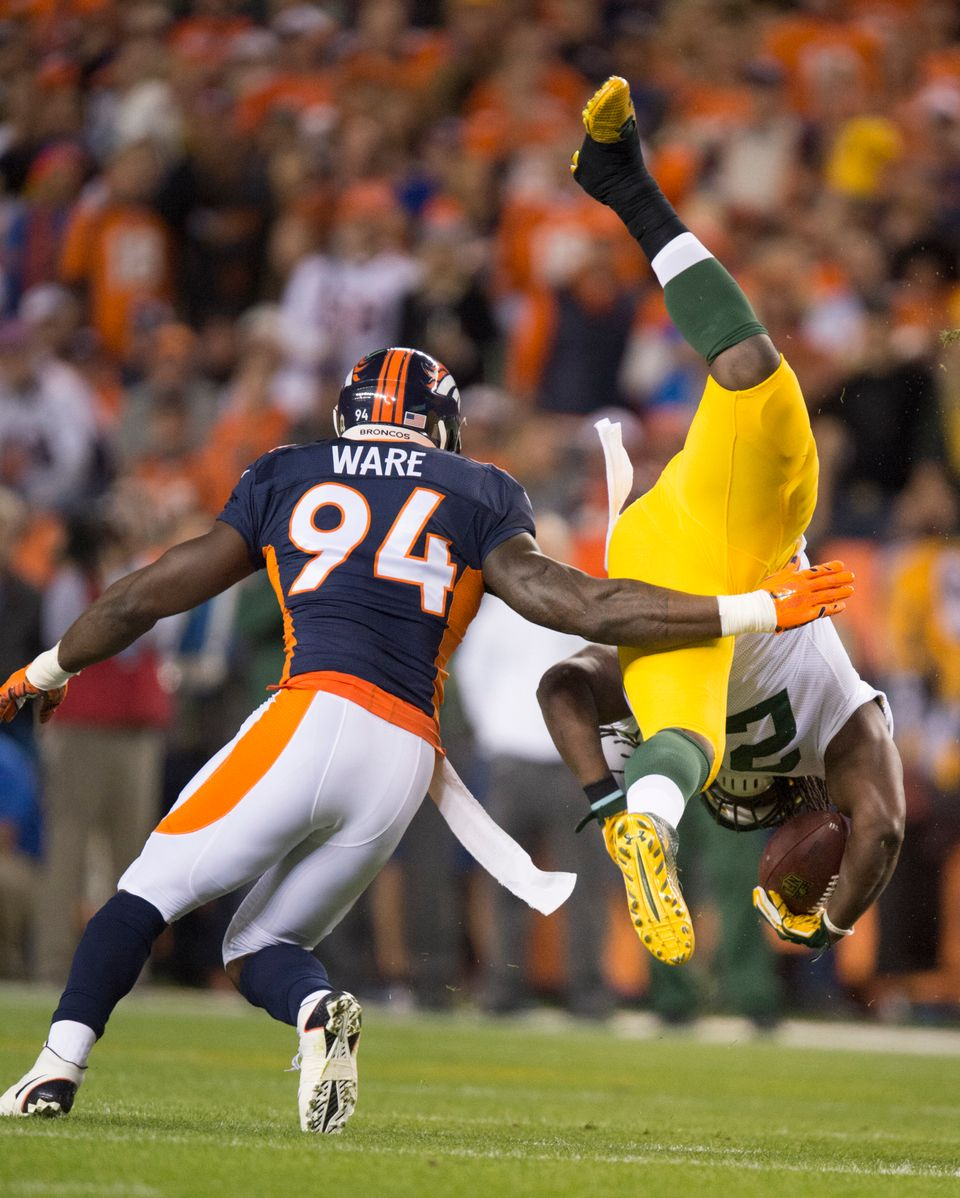 Green Bay Packers running back Eddie Lacy is flipped and brought down by Denver Broncos linebacker DeMarcus Ware during the f