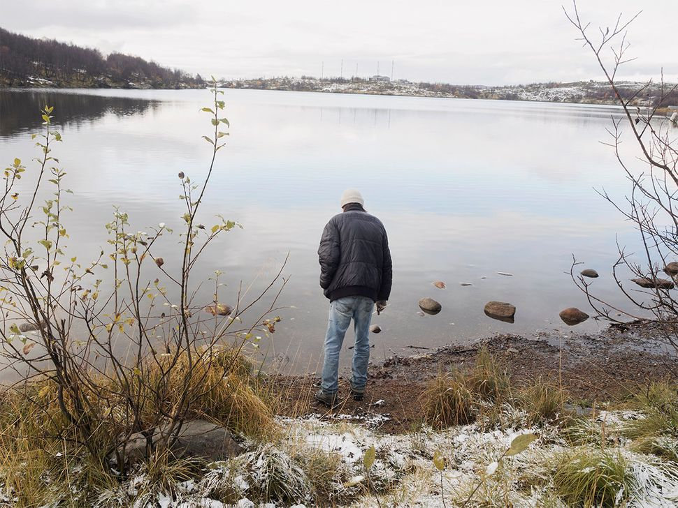 A migrant stands by Semenovskoe Lake in Murmansk, Russia. October 2015.
