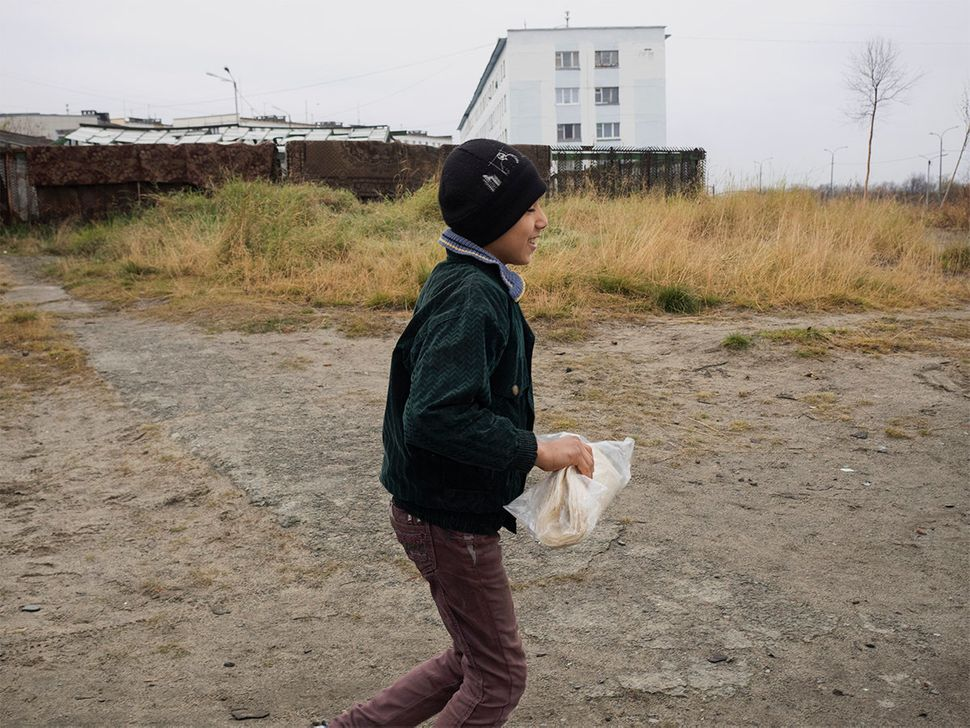 Alsaid's son in the street with fresh bread. Nickel, Russia. October 2015.