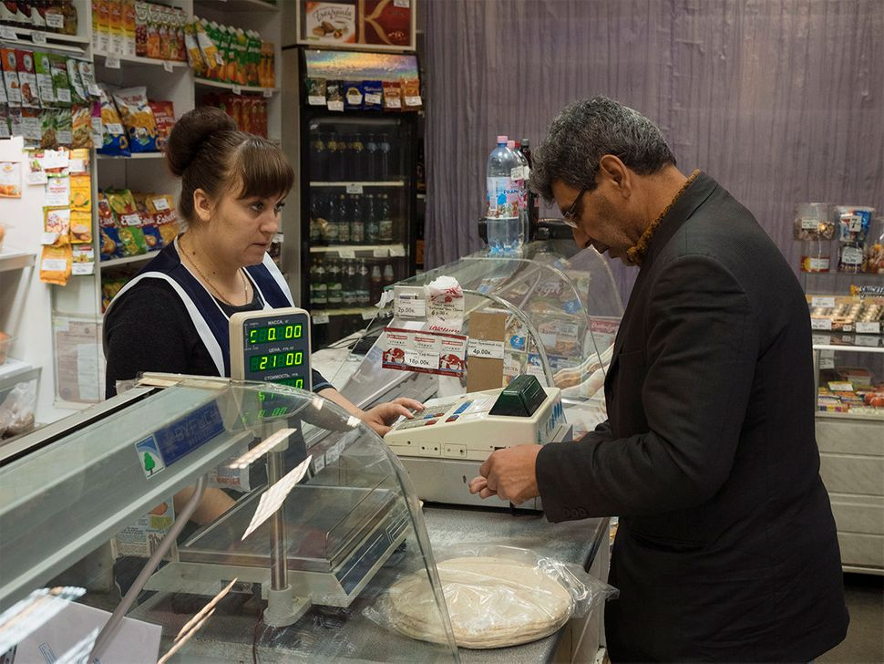 Alsaid buys bread for his family in Nikel. Nickel, Russia. October 2015.