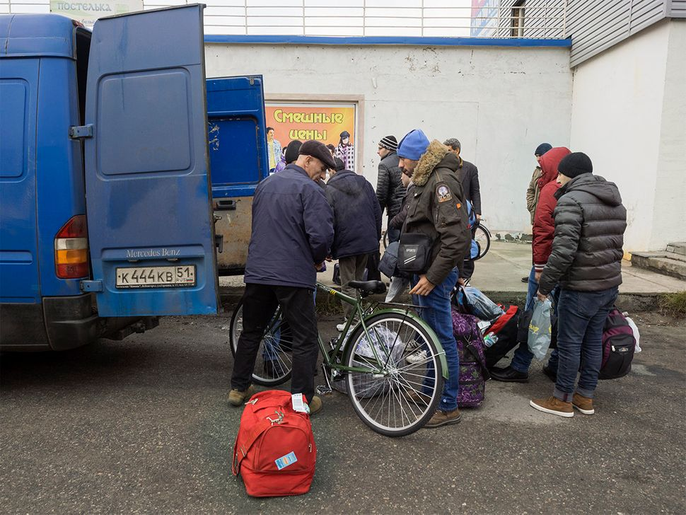 Preparations before departure. Drivers and migrants load bikes and luggage into vans. Nickel, Russia. October 2015.