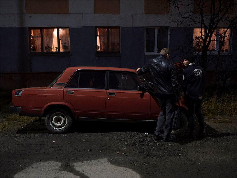 A boy fixes a car at night. Nickel, Russia. October 2015.