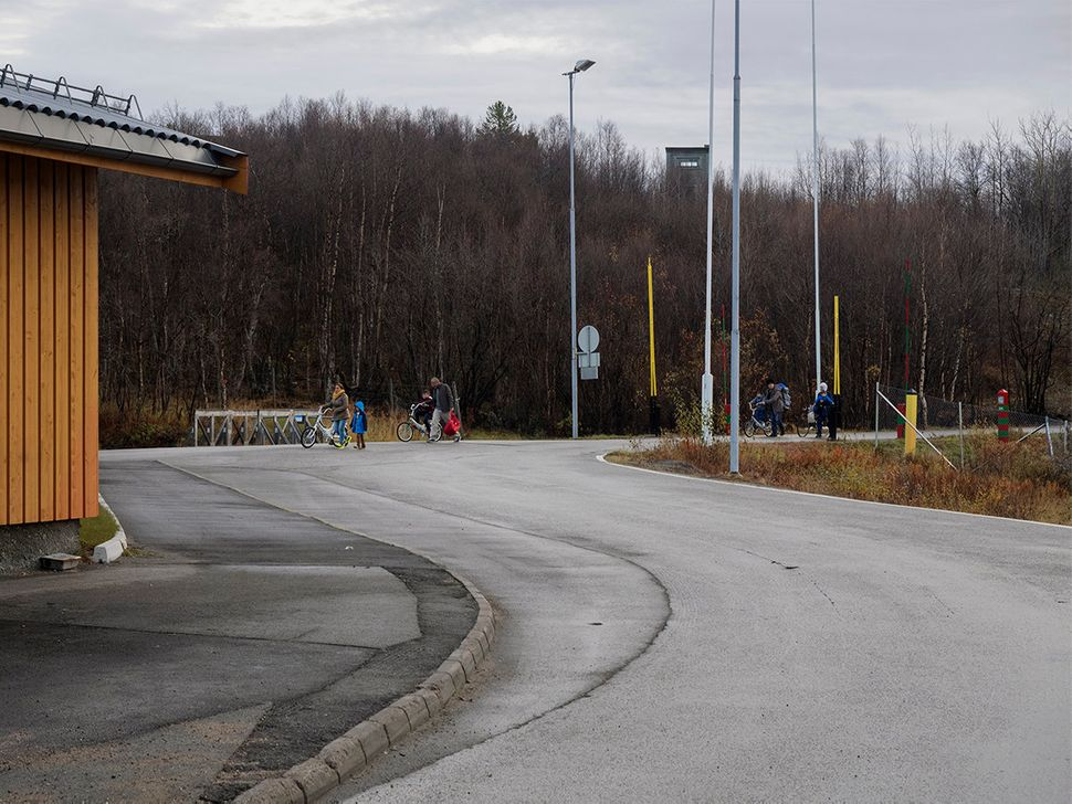 Refugees cross the Norwegian border, arriving by bike from the last Russian checkpoint. Kirkenes, Norway. October 2015.
