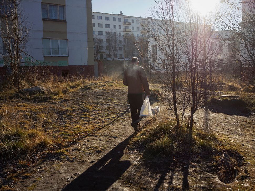A man walks among buildings in the little border town. Nickel, Russia. October 2015.