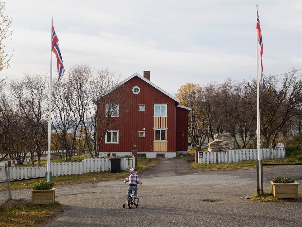 The entrance to the refugee camp in Vadso. A Syrian child rides a bike beneath Norwegian flags. Vadso, Norway. October 2015.