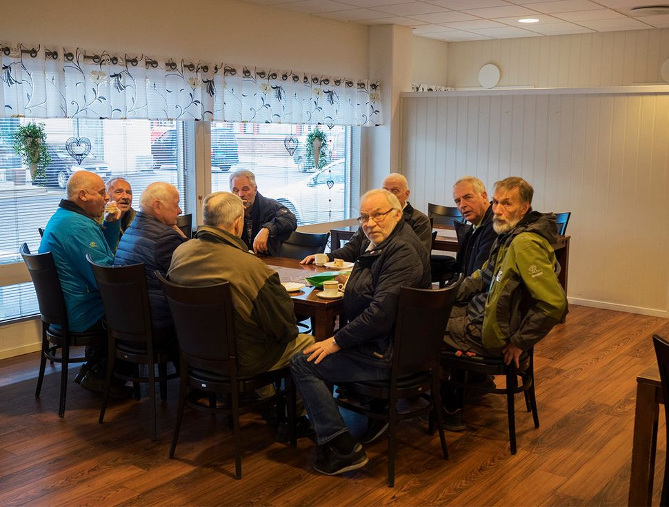 A group of elderly men sit at a bakery. People express anger about the huge influx of refugees in the country. Vadso, Norway.
