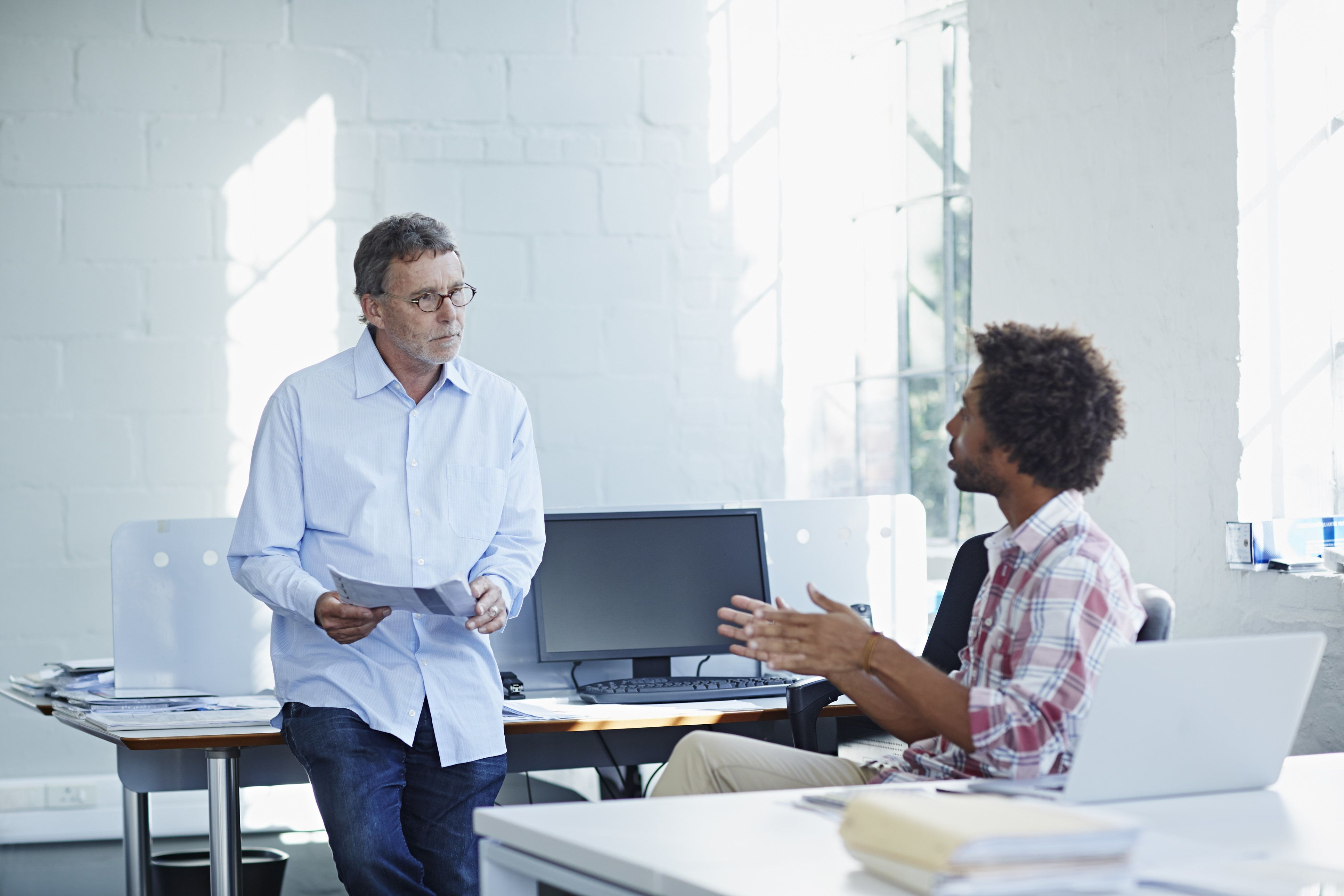 Businessman exposing project to peer in bright office