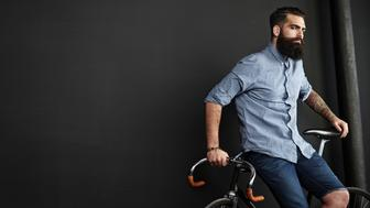 Man with bicycle on black wall background