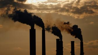 The silhouettes of emissions are seen rising from stacks of the Duke Energy Corp. Gibson Station power plant at dusk in Owensville, Indiana, U.S., on Thursday, July 23, 2015. Coal reclaimed its ranking as the top fuel for generating electricity at U.S. power plants in May, beating natural gas, which took the number one spot for the first time in April. Photographer: Luke Sharrett/Bloomberg via Getty Images