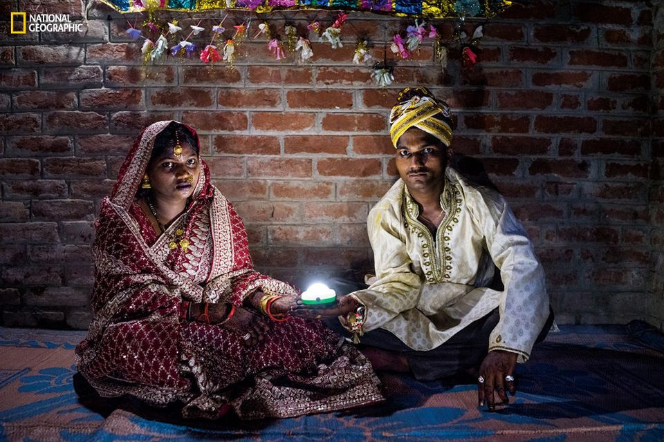 Holding a solar-powered lamp, Soni Suresh, 20, and Suresh Kashyap, 22, celebrate their marriage ceremony...
